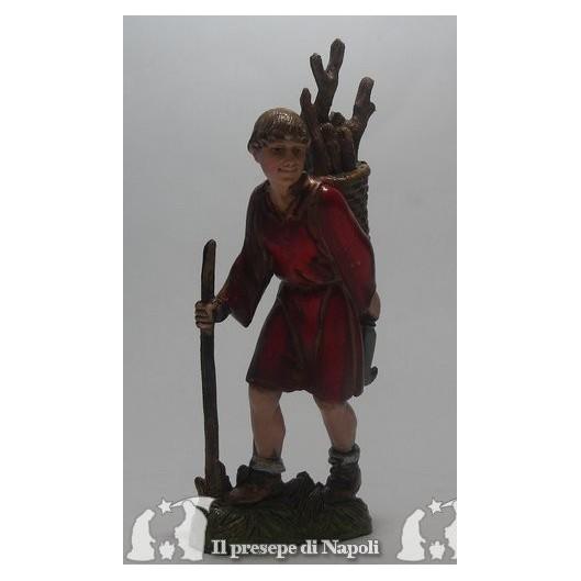 Ragazzo in cammino con legna sulle spalle