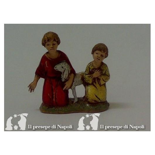 Coppia di bambini inginocchiati con pecora