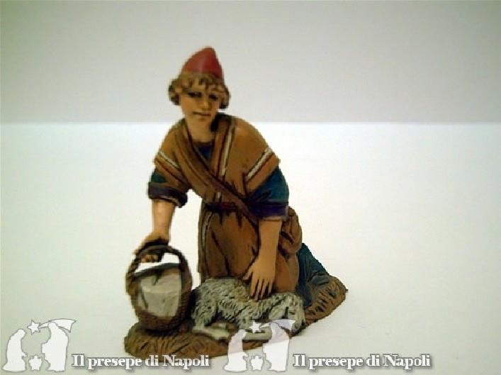 Ragazzo inginocchiato con paniere e pecora