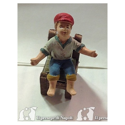 bambino seduto con cappello (sedia esclusa)