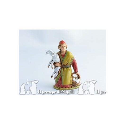 Ragazzo inginocchiato con pecora in braccio